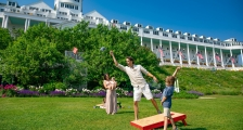 Family playing cornhole on lawn in front of Grand Hotel
