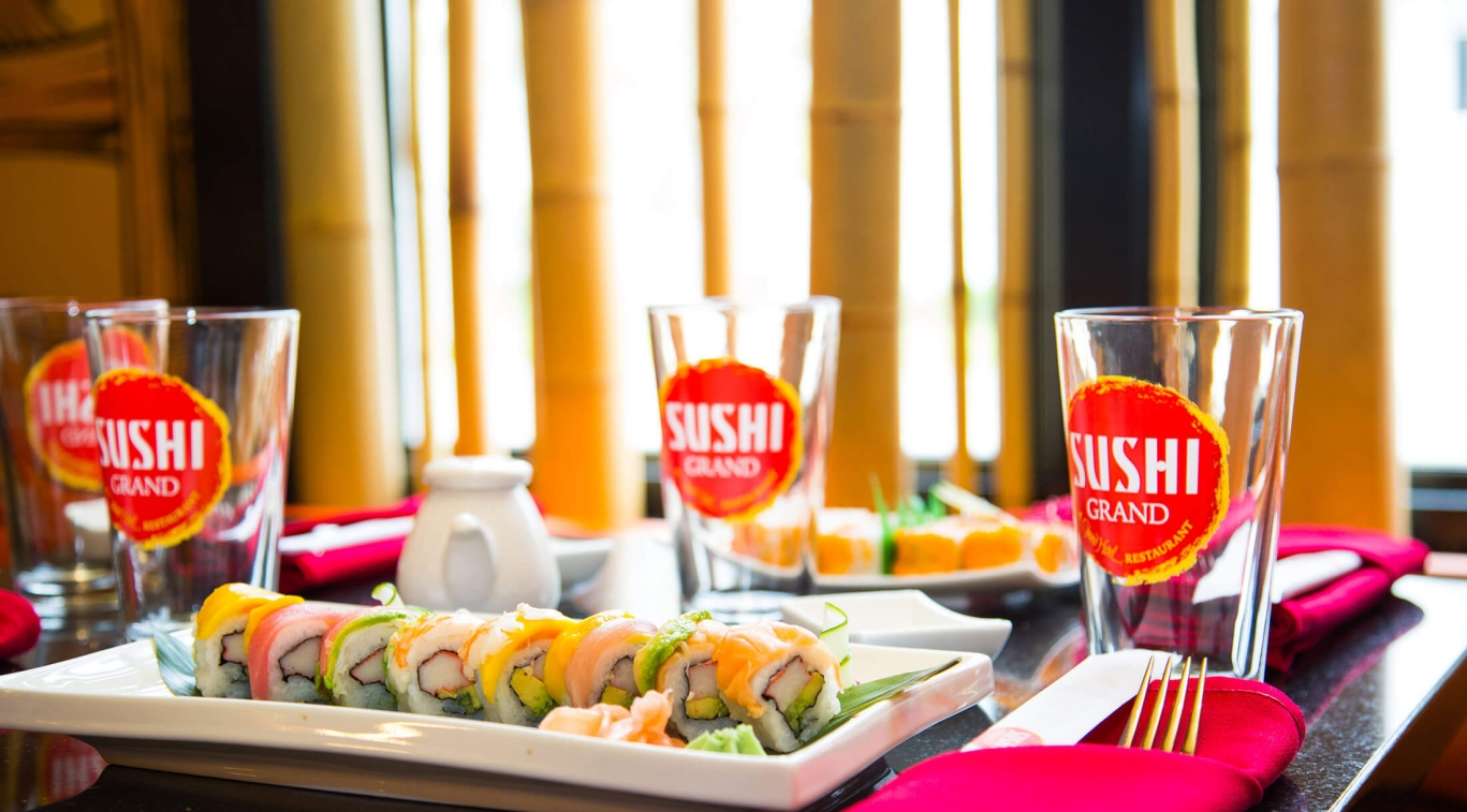A plate of sushi and some Sushi Grand glasses on a table