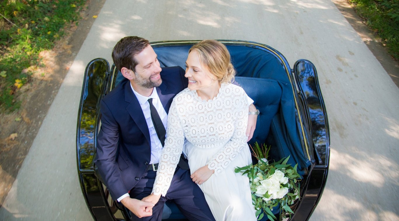 A couple sitting in a carriage on their wedding day
