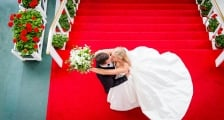 A top-view married couple kissing at the top of the steps