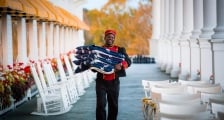 A bellman carrying American flags