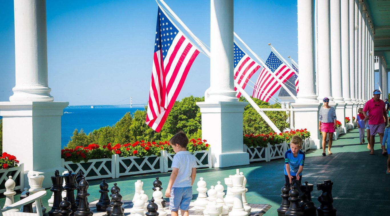 Children playing with large chess board on front porch