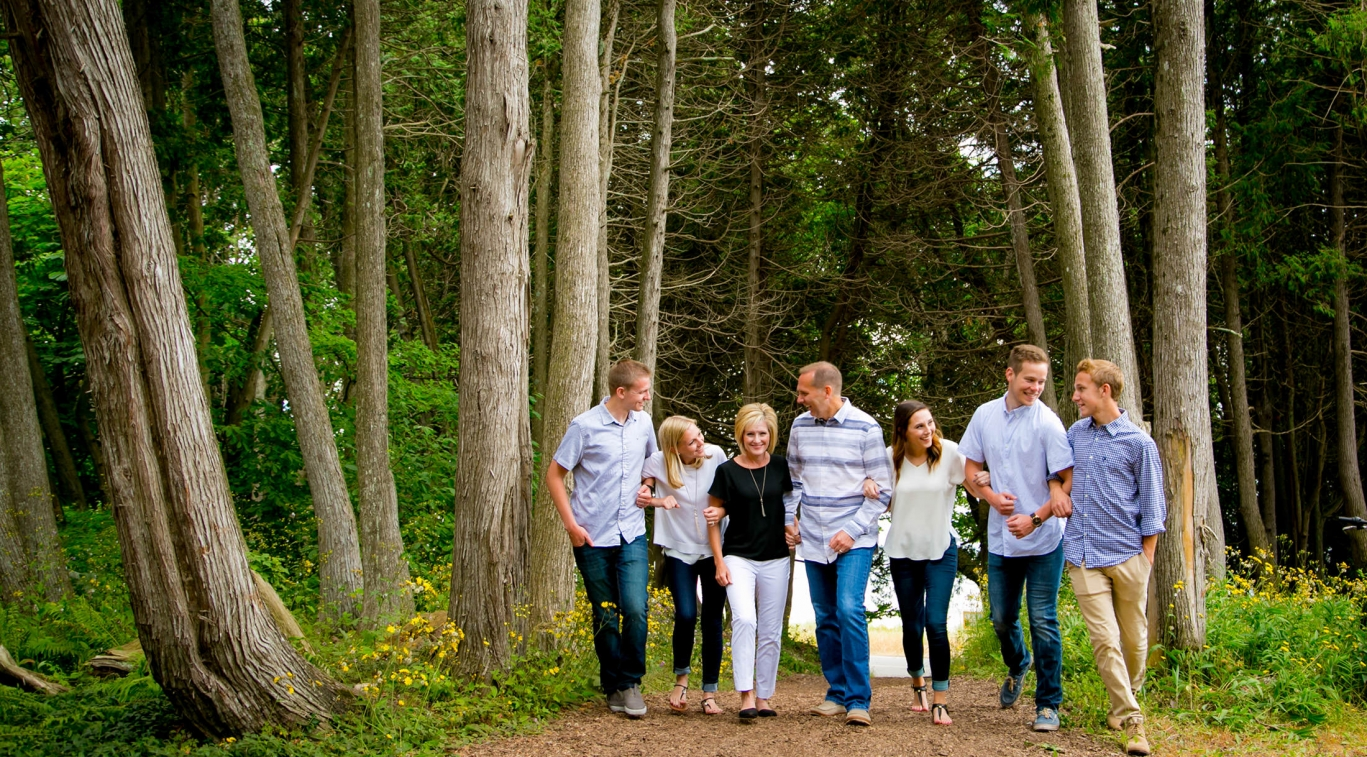 Family linking arms walking through the woods