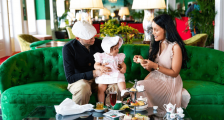 Mother and Father with child sitting on couch in Grand HOtel
