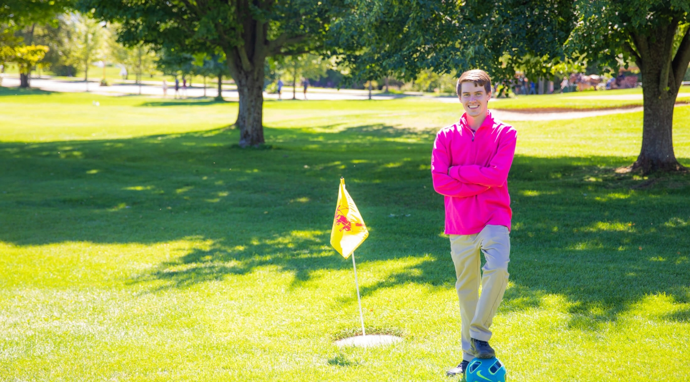 Someone posing in front of a Foot Golf hole
